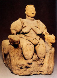 crudely made statue of a woman seated on a throne