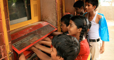 kids gathered around a computer embedded in a wall